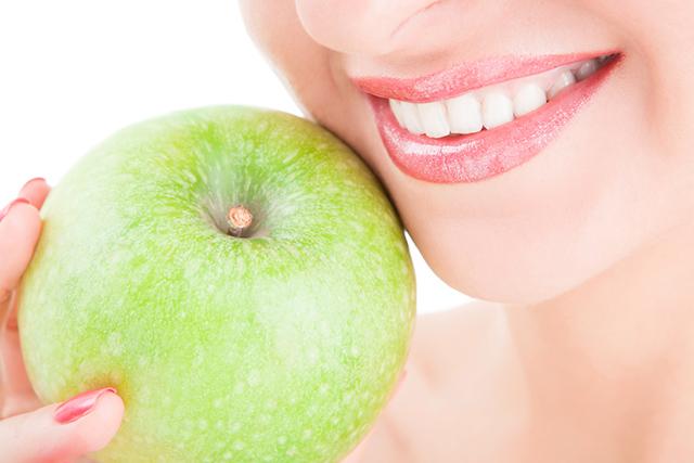 Lachender Mund neben grünem Apfel