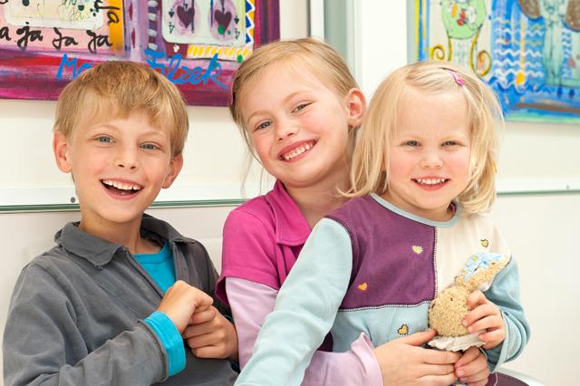 Drei lachende kleine Kinder
