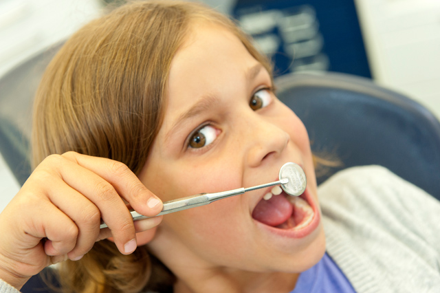 Kind lacht in Zahnarztspiegel