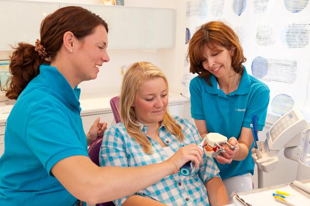 Helferinnen zeigen Patienten wie man Zähne putzt